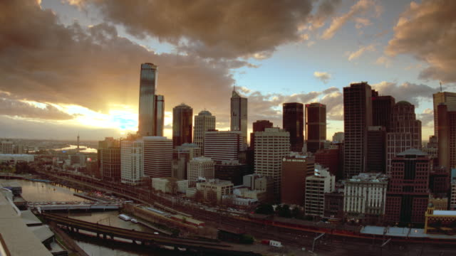 wide shot time lapse clouds moving towards camera above melbourne skyline at sunset / victoria, australia - 1999 stock videos & royalty-free footage