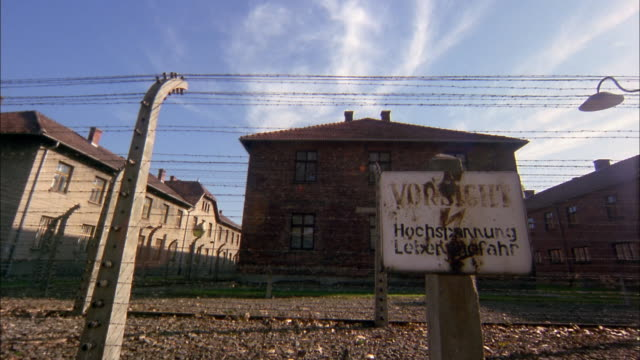 wide shot time lapse clouds over barbed wire fence and sign at birkenau concentration camp / poland - concentration camp stock videos & royalty-free footage