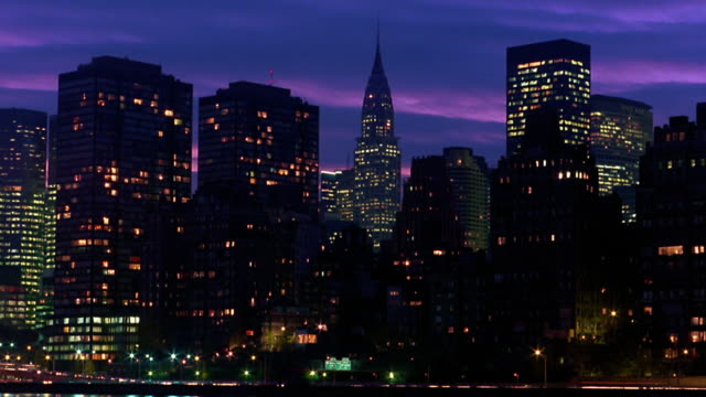Wide shot time lapse clouds over Chrysler Building and surrounding buildings from dusk to night / New York City