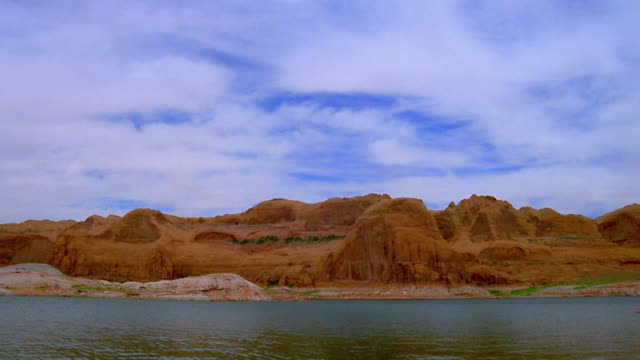 wide shot time lapse clouds over lake powell with red rock formations on shoreline / utah - lake powell stock videos & royalty-free footage