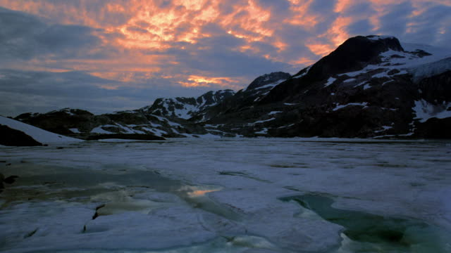 Wide shot time lapse clouds over partially frozen lake with mountains and snow in background at dusk / British Columbia