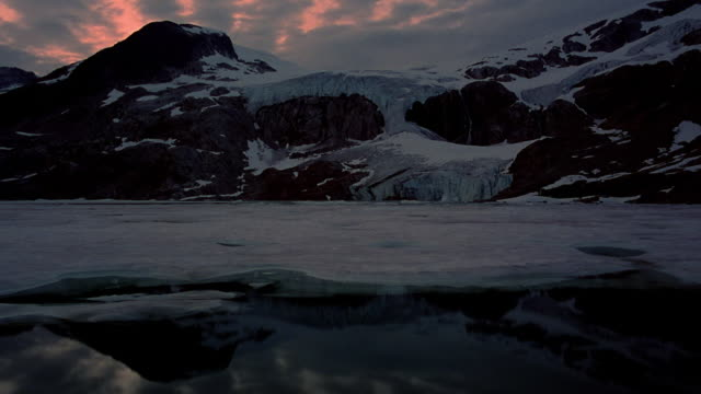 Wide shot time lapse clouds over partially frozen lake with snowy mountains in background at dusk / British Columbia