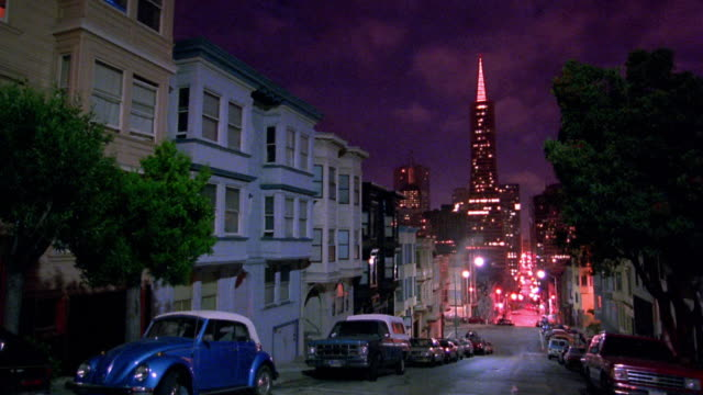 Wide shot time lapse clouds over residential street with light traffic at night / Transamerica Pyramid in background / California