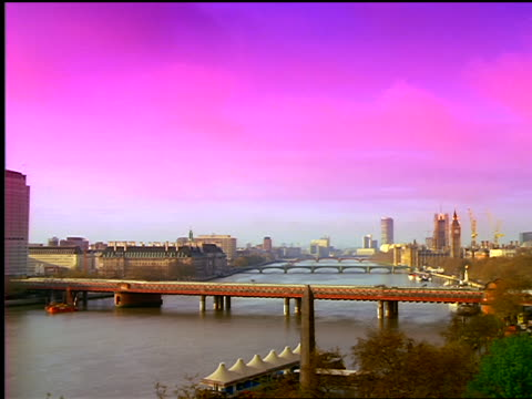 wide shot time lapse clouds over thames river + train traffic over lambeth railroad bridge / london, england - lambeth stock-videos und b-roll-filmmaterial