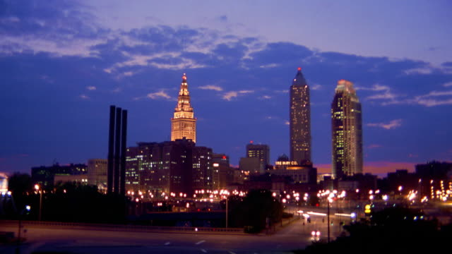 Wide shot time lapse clouds over traffic on highway and streets with Cleveland skyline in background at dusk / Ohio