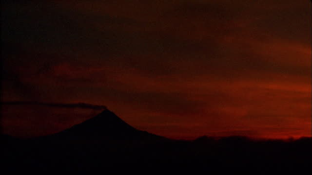 wide shot time lapse clouds passing mount merapi volcano with smoke coming from it at dawn / java, indonesia - murmursofearth点の映像素材/bロール