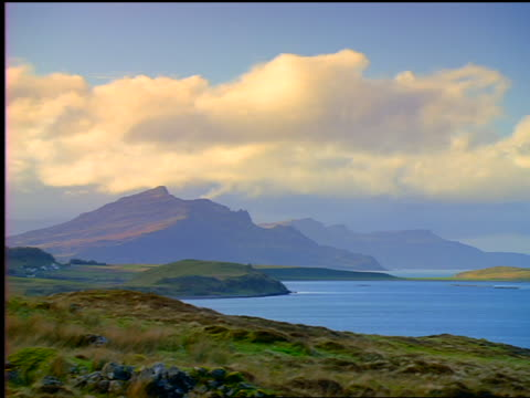 wide shot time lapse clouds passing over mountains + lake / isle of skye, scotland - ヘブリディーズ点の映像素材/bロール