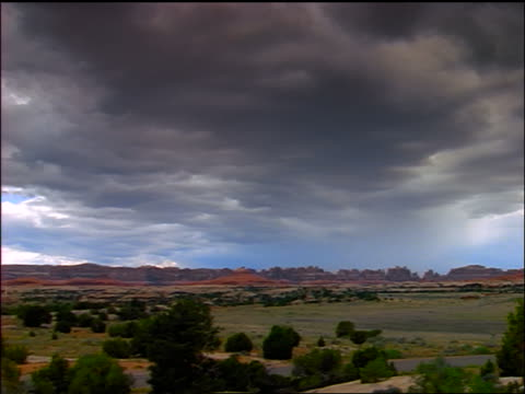 wide shot pan time lapse clouds passing over plains + rocky landscape / canyonlands national park, utah - canyonlands national park stock videos & royalty-free footage