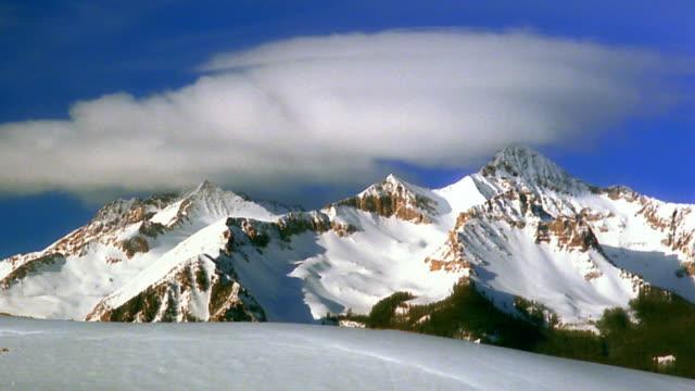 wide shot time lapse clouds rolling above snow-covered rocky mountain range / colorado - fast kamera bildbanksvideor och videomaterial från bakom kulisserna