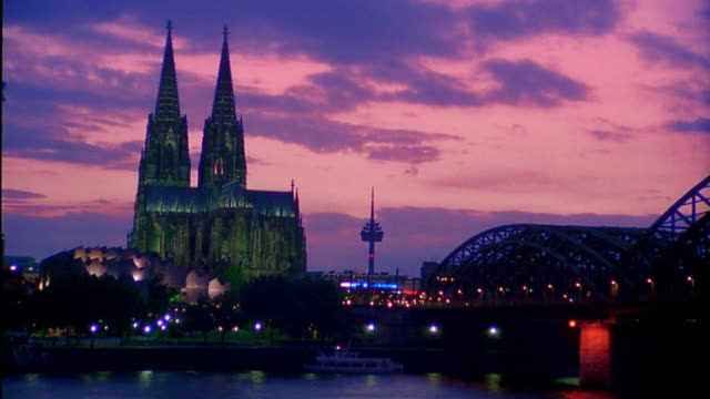 Wide shot time lapse clouds rolling over Cologne Cathedral and Rhine River with Fernmeldeturm in background at dusk / Germany