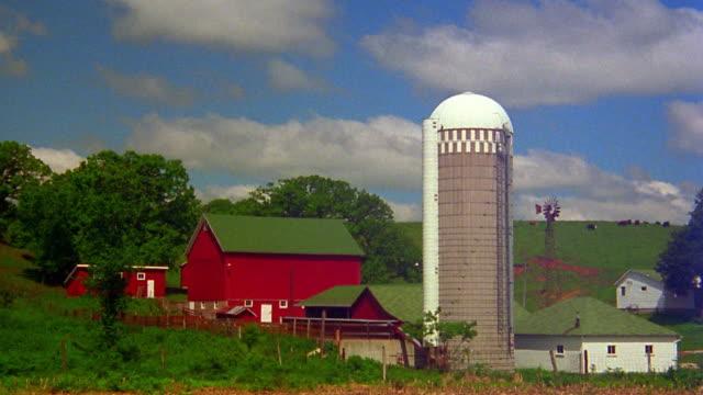 vidéos et rushes de wide shot time lapse clouds rolling over farm with silo / iowa - silo