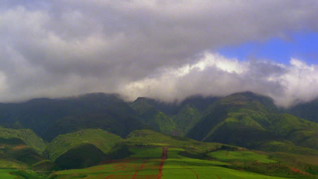 wide shot time lapse clouds rolling over green mountains, hills and countryside / hawaii - 1985 stock videos & royalty-free footage
