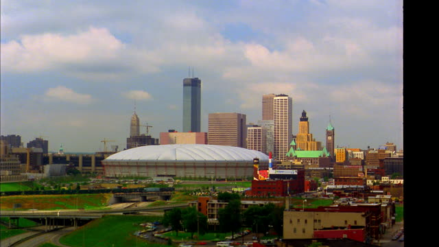 wide shot time lapse clouds rolling over metrodome + minneapolis skyline with traffic on highway in foreground / mn - 1983 stock videos & royalty-free footage
