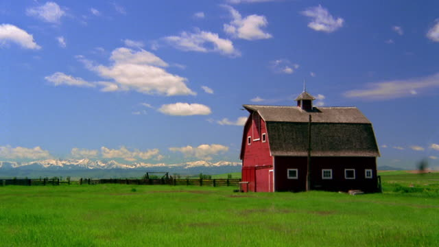 wide shot time lapse clouds rolling over red barn on grassy field / wyoming - barn stock videos & royalty-free footage