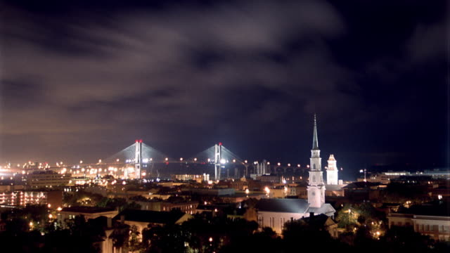 Wide shot time lapse clouds rolling over Savannah with Talmadge Memorial Bridge in background at night / Georgia