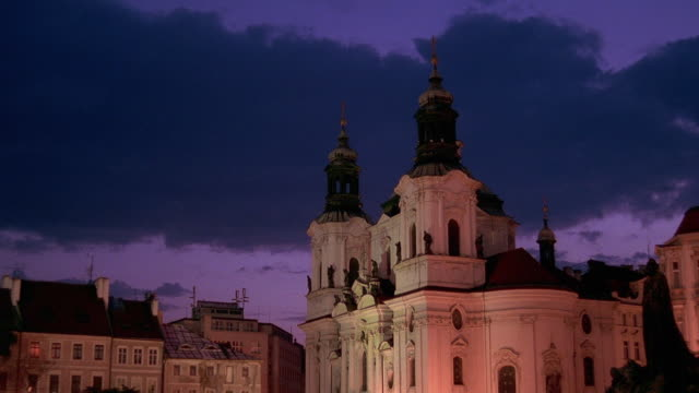 wide shot time lapse clouds rolling over st nicholas church and buildings at dusk in old town square / prague - mala strana stock videos and b-roll footage