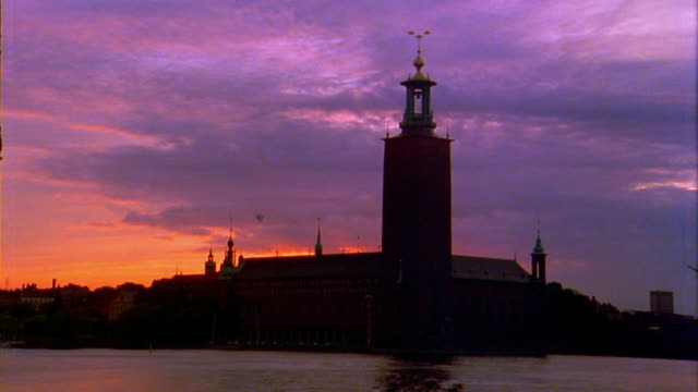 wide shot time lapse clouds rolling over stockholm cathedral at dusk with lake malaren in foreground / sweden - famous place stock videos & royalty-free footage