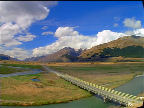 wide shot time lapse clouds + shadows over in Mararoa River Valley / cars on highway/ South Island, New Zealand