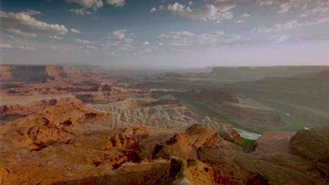 wide shot pan time lapse clouds + shadows over weathered canyon / canyonlands national park, utah - キャニオンランズ国立公園点の映像素材/bロール