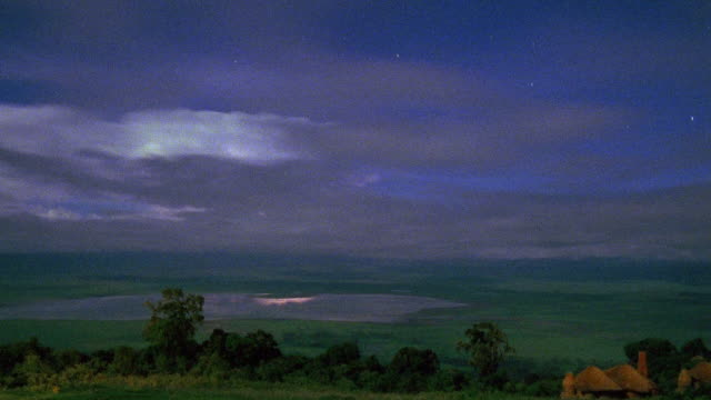 Wide shot time lapse dark clouds moving over lake and plains / Ngorongoro Crater, Serengeti National Park