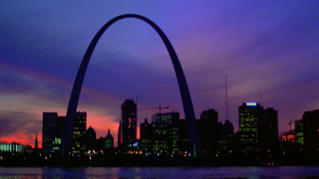 Wide shot time lapse dusk to night Gateway Arch and St. Louis skyline with Mississippi River in foreground / Missouri