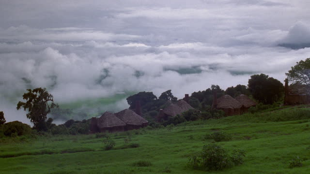 Wide shot time lapse fog moving uphill towards straw huts / Serengeti National Park, Tanzania, Africa