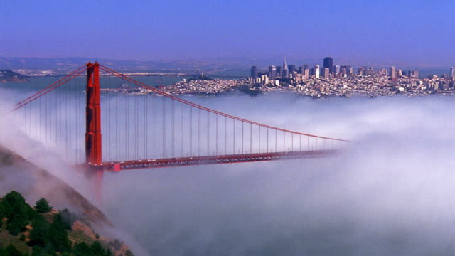 wide shot time lapse fog rolling over golden gate bridge with san francisco in background / california - golden gate bridge stock-videos und b-roll-filmmaterial