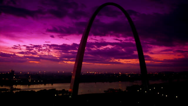 TINTED wide shot time lapse Gateway Arch + Mississippi River at dawn / St. Louis, MO