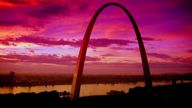 tinted wide shot time lapse gateway arch + mississippi river at dawn / st. louis, mo - ミズーリ州 セントルイス点の映像素材/bロール
