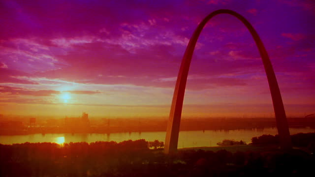 TINTED wide shot time lapse Gateway Arch + Mississippi River at dawn with sunrise in background / St. Louis, MO