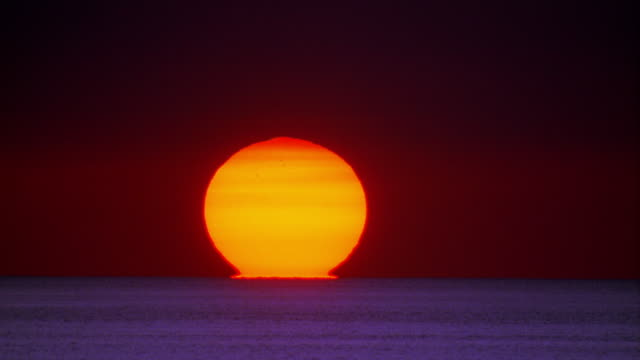wide shot time lapse large sun setting over ocean / hawaii - meerlandschaft stock-videos und b-roll-filmmaterial