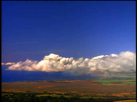 wide shot time lapse low clouds in blue sky over landscape with coastline and pacific ocean / hawaii - 1985 stock videos & royalty-free footage