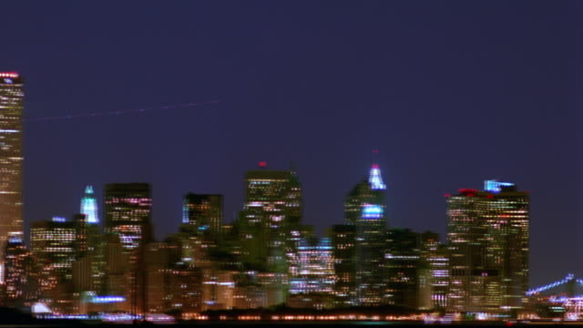 wide shot PAN time lapse Manhattan skyline with Statue of Liberty, World Trade Center, + Empire State at night / NYC