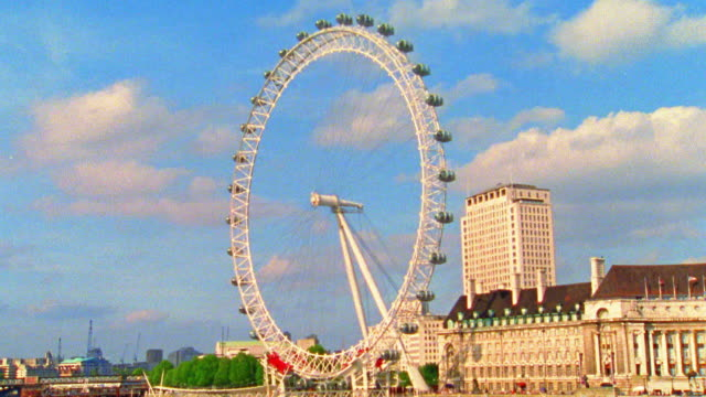 Wide shot time lapse Millennium London Eye Ferris Wheel turning with boats moving on Thames River in foreground / England