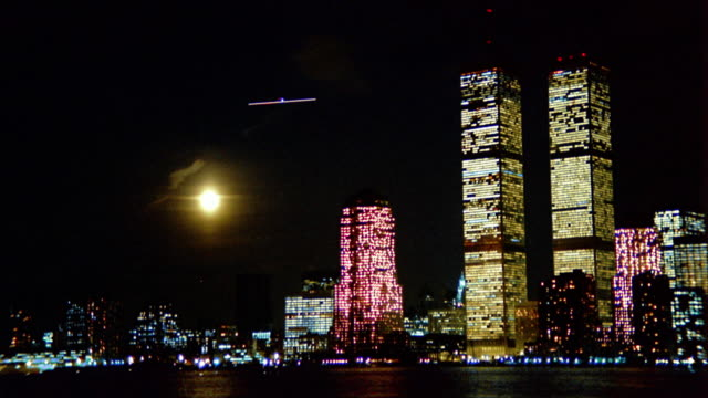 wide shot time lapse moonrise and clouds behind lower manhattan with world trade center / new york city - world trade center manhattan stock-videos und b-roll-filmmaterial