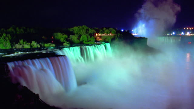 vídeos y material grabado en eventos de stock de wide shot time lapse niagara falls with mist at night with changing colored lights shining on falls / ontario, canada - cataratas del niágara