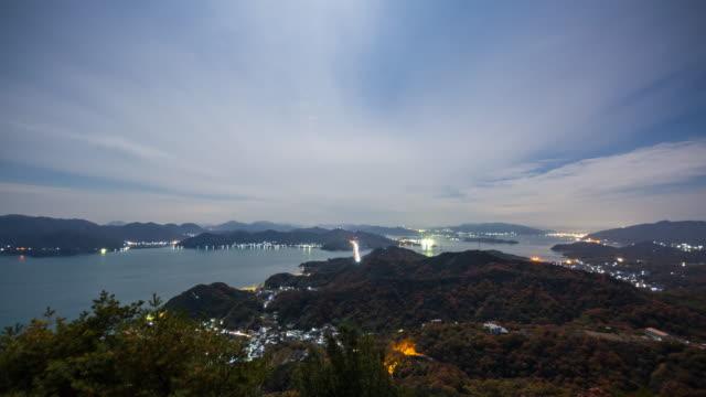 vidéos et rushes de laps de temps large coup d'un trafic, faire la navette entre les îles sur un pont dans la nuit - hiroshima prefecture