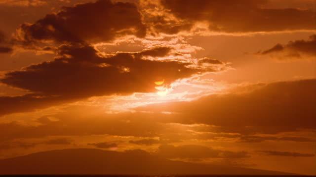wide shot time lapse orange clouds moving over dark ocean / god rays from setting sun in darkening sky / hawaii - romantische stimmung stock-videos und b-roll-filmmaterial