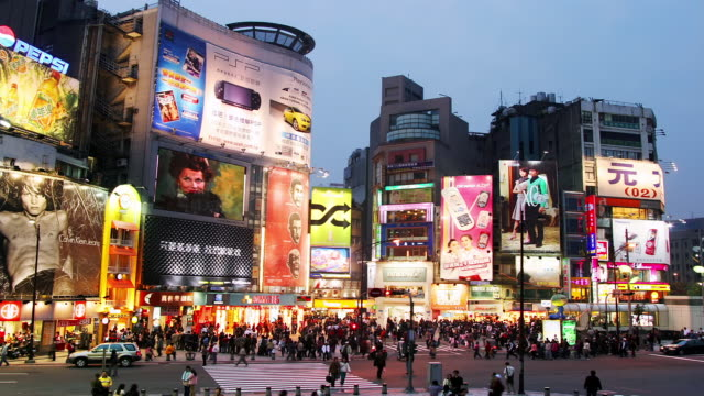 wide shot time lapse people and traffic moving beneath bright signs + screens in Ximen district / Taipei, Taiwan