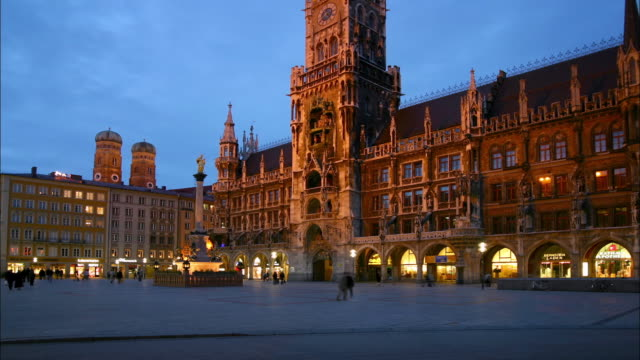 vidéos et rushes de wide shot time lapse people walking near the rathaus at twilight / munich, germany - rathaus