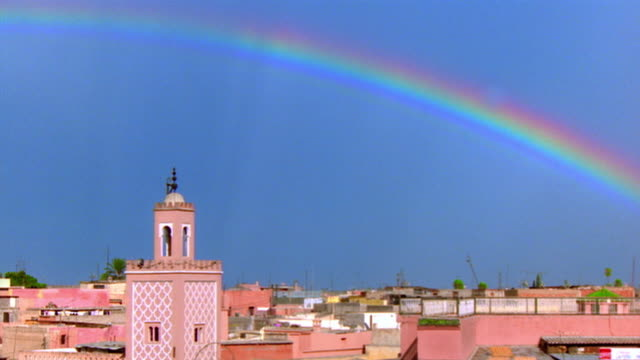 wide shot time lapse rainbow brightening in blue sky over city rooftops / marrakesh, morocco - minaret stock videos & royalty-free footage