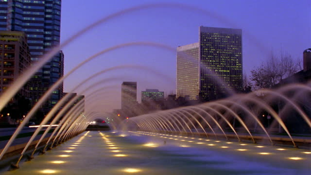 Wide shot time lapse row of fountains creating arcs with buildings and traffic in background at dusk/Century City, Los Angeles, California