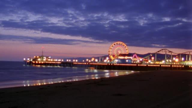 vidéos et rushes de wide shot time lapse santa monica pier lit at night w/ferris wheel and amusement park / california - santa monica