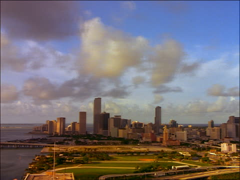 vidéos et rushes de wide shot time lapse shadows + clouds over miami skyline - cinématographie
