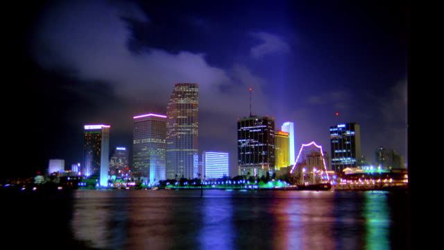 wide shot time lapse skyline at night with boats moving on water in foreground at night / Miami, Florida