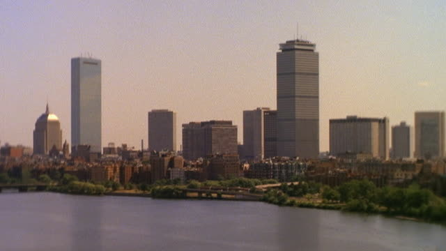 wide shot time lapse skyline of boston with charles river in foreground / night to day to night with lightning / massachusetts - back bay boston stock videos & royalty-free footage