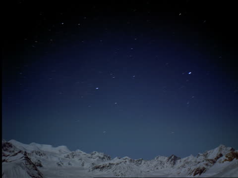 wide shot time lapse starfield at night over snowy mountains with northern lights (aurora borealis) / Alaska