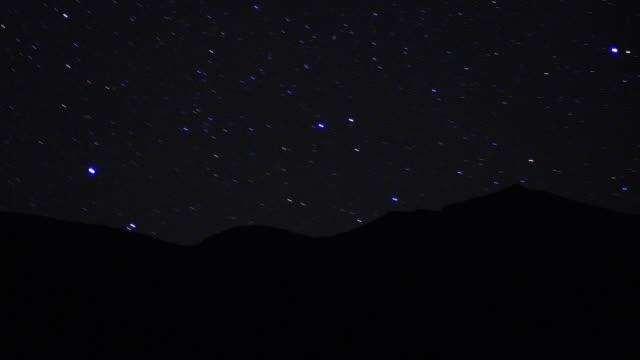 wide shot time lapse stars moving behind silhouetted sand dunes at night / sahara desert, morocco - sahara desert stock videos & royalty-free footage