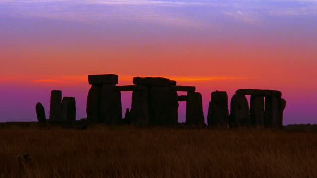wide shot time lapse stonehenge rock monument with field in foreground at dusk / wiltshire, england - obelisk stock videos & royalty-free footage