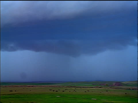wide shot time lapse storm clouds, rain + lightning over plains with animals grazing - 1998 stock videos and b-roll footage
